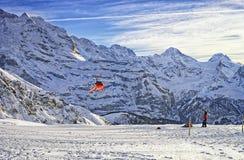 飞行在瑞士滑雪胜地的红色直升机在少女峰mounta附近 库存图片