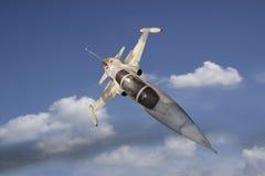 飞行在白色云彩的军用喷气机 免版税图库摄影