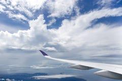 飞行在白色云彩的平面翼 免版税库存图片