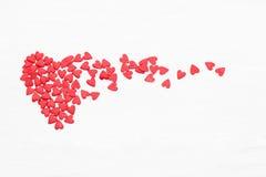飞行在白色背景的许多一点红色心脏 免版税库存照片