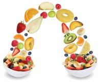 飞行在碗的水果沙拉用果子喜欢苹果,桔子,豌豆 免版税库存照片