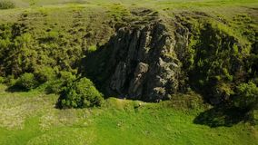 飞行在美丽如画的谷、绿色领域和小山、岩石峭壁和山,岩石的照相机空中英尺长度 股票视频