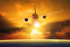 飞行在美丽的日落天空的客机 库存图片