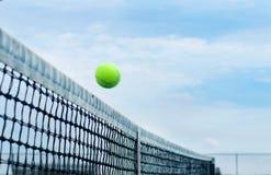 飞行在背景蓝天的中间净法院的网球 图库摄影