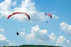 飞行在蓝天的两个滑翔伞以云彩为背景 库存照片