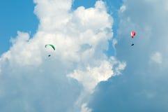 飞行在蓝天的两个滑翔伞以云彩为背景 免版税库存图片