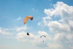 飞行在蓝天的两个滑翔伞以云彩为背景 库存图片