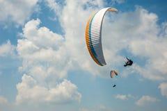 飞行在蓝天的两个滑翔伞以云彩为背景 免版税图库摄影
