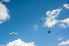 飞行在蓝天的两个滑翔伞反对云彩 免版税图库摄影