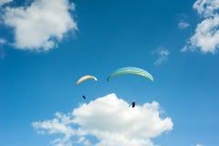 飞行在蓝天的两个滑翔伞反对云彩 库存照片