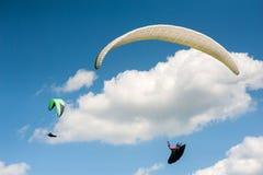 飞行在蓝天的两个滑翔伞反对云彩 免版税库存图片