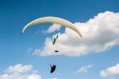 飞行在蓝天的两个滑翔伞反对云彩 图库摄影