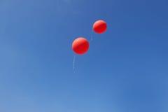 飞行在蓝天的两个红色气球 免版税库存图片