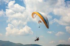飞行在蓝天背景的两个滑翔伞  免版税库存图片