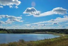 飞行在蓝色湖的云彩在夏天 免版税库存图片
