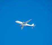 飞行在蓝色背景,不用在天空的一朵云彩 免版税库存照片