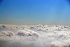 飞行在蓬松云彩在清楚的太阳下 免版税库存图片