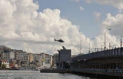 飞行在金黄垫铁和加拉塔桥梁的直升机 免版税库存图片