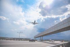飞行在高速公路的客机的特写镜头反对天空蔚蓝 免版税库存照片
