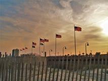 飞行在默特尔海滩日落的旗子 库存图片