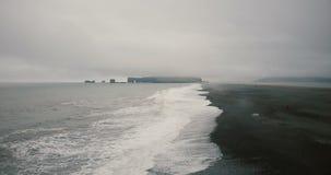 飞行在黑火山的海滩的直升机在冰岛 水、山、波浪和雾的美好的风景 影视素材