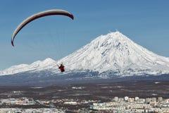 飞行在活火山背景的城市的滑翔伞  库存照片