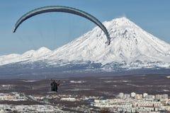 飞行在活火山背景的城市的滑翔伞  免版税库存图片