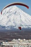 飞行在活火山背景的城市的滑翔伞  免版税图库摄影