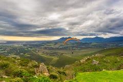 飞行在绿色山的滑翔伞在开普敦,南非附近 冬天季节,多云和剧烈的天空 无法认出 库存照片