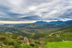 飞行在绿色山的滑翔伞在开普敦,南非附近 冬天季节,多云和剧烈的天空 无法认出 库存图片
