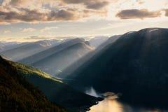 飞行在Aurlandfjord,挪威的滑翔伞剪影 免版税库存照片