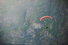 飞行在Aurlandfjord,挪威的滑翔伞剪影 免版税库存图片