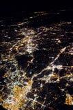 飞行在citiesbelow的晚上 库存图片