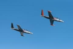 飞行在Kaivopuisto飞行表演的两架银色Fouga Magister喷气机 免版税库存图片