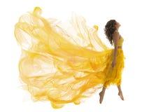 飞行妇女升空跃迁,在飞行黄色礼服的时装模特儿 免版税库存图片