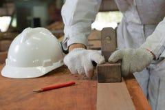飞行木头的板条工作者的手使用一台手整平机在木匠业车间 免版税库存照片