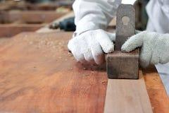 飞行木头的板条木匠使用一台手整平机在木匠业车间 免版税图库摄影