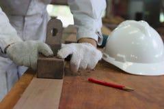 飞行木头的板条木匠的手使用一台手整平机在木匠业车间 库存图片
