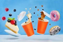 飞行杯与多彩多姿的油炸圈饼和cheesecak的咖啡 免版税库存照片