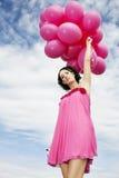 飞行桃红色妇女的气球 库存照片