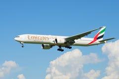 飞行波音777-300 (A6-EGU)在云彩上的阿联酋国际航空 图库摄影