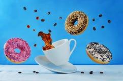 飞行的多彩多姿的油炸圈饼和一杯咖啡 免版税库存图片