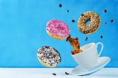 飞行的多彩多姿的油炸圈饼和一杯咖啡 库存照片