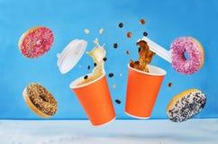 飞行的多彩多姿的油炸圈饼和杯咖啡 库存照片