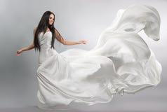 飞行的白色礼服的美丽的女孩 织品流 轻的白色布料飞行 库存照片
