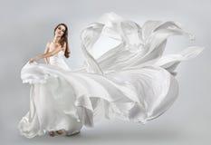 飞行的白色礼服的美丽的女孩 免版税库存照片