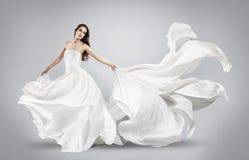 飞行的白色礼服的美丽的女孩 库存图片