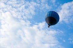 飞行的蓝色热空气气球在多云天空 免版税库存照片