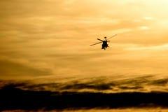 飞行直升机日落 免版税库存图片
