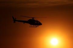 飞行直升机日落 免版税图库摄影